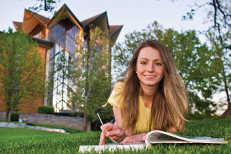 Photo of a student sitting in a lawn with a book