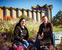 Photo of two students in front of a campus building