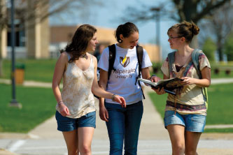Photo of three students walking on campus